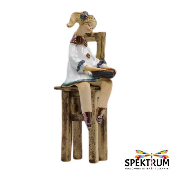 Dziewczynka z książką siedząca na krześle